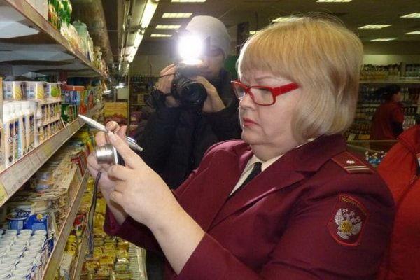 Сотрудник Роспотребнадзора фотографирующий товар на полках в магазине